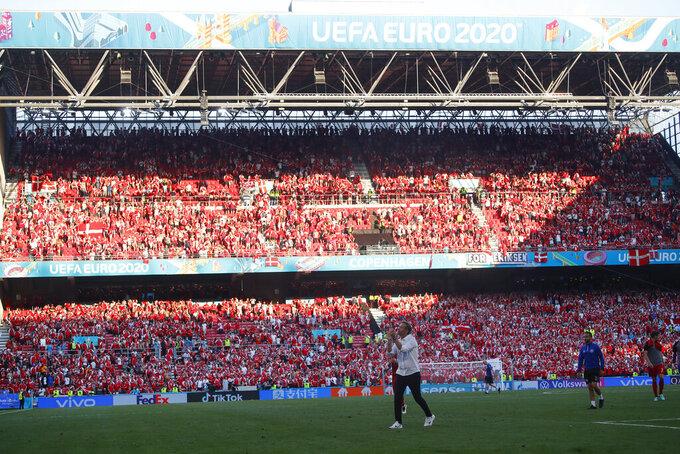 Denmark's managaer Kasper Hjulmand applauds fans as he walks off the pitch after the Euro 2020 soccer championship group B match between Denmark and Belgium, at the Parken stadium in Copenhagen, Thursday, June 17, 2021. Belgium won 2-1. (Wolfgang Rattay, Pool via AP)