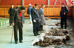 FILE - In this Oct. 9, 1996. file photo, Bosnian Muslims trying to recognize their relatives killed by Bosnian Serbs in 1992, inside a sport hall in Kljuc, 160 kms (100mls) north-west of Sarajevo, Bosnia. While it brought an end to the fighting, the Dayton peace agreement baked in the ethnic divisions, establishing a complicated and fragmented state structure with two semi-autonomous entities, Serb-run Republika Srpska and a Federation shared by Bosniak and Croats, linked by weak joint institutions. (AP Photo/Darko Bandic, File)
