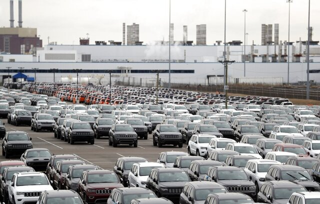 FILE - In this Feb. 26, 2019, file photo, Jeep vehicles are parked outside the Jefferson North Assembly Plant in Detroit. Defying a wave of layoffs that has sent the U.S. job market into its worst catastrophe on record, at least one major industry is making a comeback: Tens of thousands of auto workers are returning to factories that have been shuttered since mid-March due to fears of spreading the coronavirus. (AP Photo/Carlos Osorio, File)
