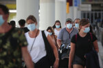 Passengers wearing face masks arrive at Son Sant Joan airport on the Spanish Balearic Island of Mallorca, Spain, Monday, July 27, 2020. Britain has put Spain back on its unsafe list and announced Saturday that travelers arriving in the U.K. from Spain must now quarantine for 14 days. (AP Photo/Joan Mateu)