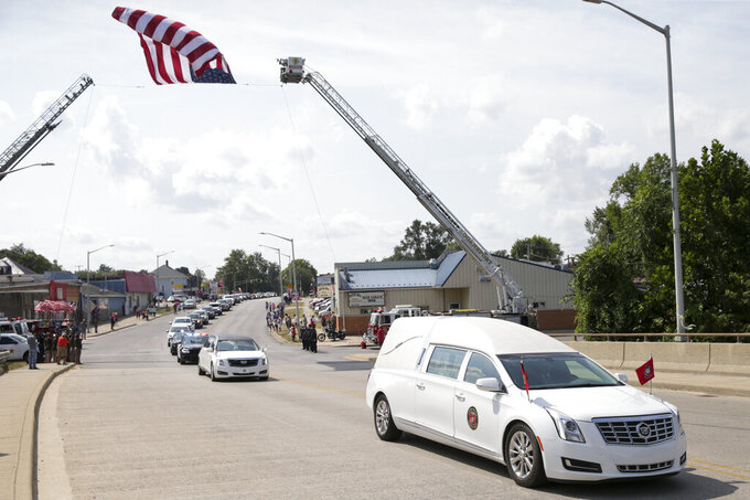 The funeral procession for Marine Cpl. Humberto Sanchez passes under an American flag, Tuesday, Sept. 14, 2021 in Logansport, Ind. Sanchez was one of 13 U.S. service members to die in an explosion during evacuation efforts in Afghanistan. (Nikos Frazier/Journal & Courier via AP)