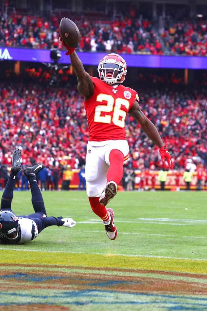 Kansas City Chiefs running back Damien Williams (26) leaps across the goal line, scoring the Chiefs first touchdown of the game during an NFL divisional playoff game against the Houston Texans, Sunday, Jan. 12, 2020 in Kansas City. The Chiefs defeated the Texans 51-31 (Margaret Bowles via AP)