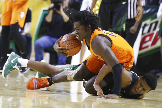 Oklahoma State guard Isaac Likekele grabs a loose ball while falling onto Baylor guard Jared Butler, right, during the second half of an NCAA college basketball game Wednesday, March 6, 2019, in Waco, Texas. (Rod Aydelotte/Waco Tribune Herald via AP)