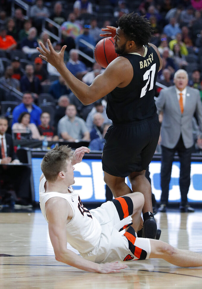 Colorado's Evan Battey, top, drives into Oregon State's Gligorije Rakocevic during the first half of an NCAA college basketball game in the quarterfinal round of the Pac-12 men's tournament Thursday, March 14, 2019, in Las Vegas. (AP Photo/John Locher)