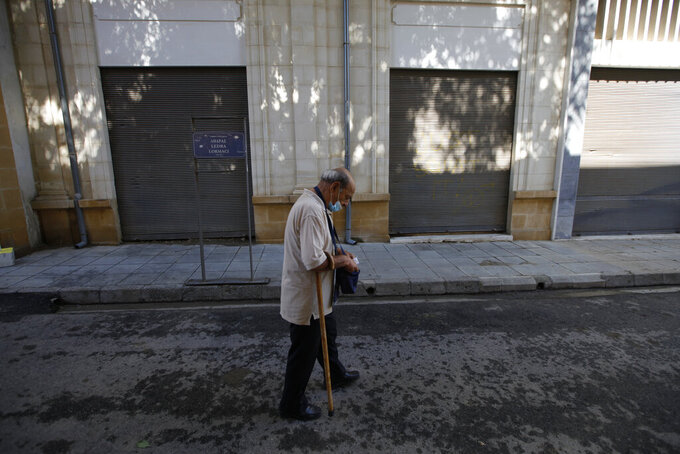 An elderly man wearing protective face mask, holds his PCR test as he crosses from the Geek Cypriot south, to the Turkish occupied north, at Ledra checkpoint in divided capital Nicosia, Cyprus, Friday, June 4, 2021. Ethnically split Cyprus took a key step toward a return to its normal rhythms of life amid the pandemic on Friday when nine crossing points along a United Nations-controlled buffer zone were reopened, enabling ordinary Cypriots to cross the divide. (AP Photo/Petros Karadjias)
