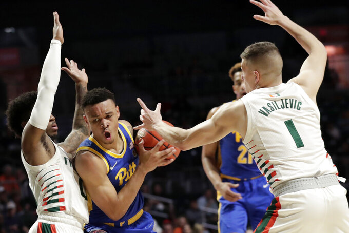Pittsburgh guard Trey McGowens, center, is defended by Miami guards Chris Lykes, left, and Dejan Vasiljevic (1) during the first half of an NCAA college basketball game, Sunday, Jan. 12, 2020, in Coral Gables, Fla. (AP Photo/Lynne Sladky)