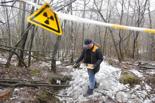 In this photo taken on Thursday, Feb. 27, 2020, Alexei Ozerov, physicist and activist fighting against turning a nuclear waste repository into a construction site of a highway, measures radiation levels at the place in southeastern Moscow, Russia. Activists in Moscow are vowing to persist with a campaign against plans to bulldoze a highway through a radioactive waste site, despite a police crackdown with mass detentions. The campaign started two months ago as a small grassroots effort to stop construction of a multi-lane motorway that is supposed to go through a plot of land where at least 60,000 tons of nuclear waste are buried. (AP Photo/Alexander Zemlianichenko Jr)