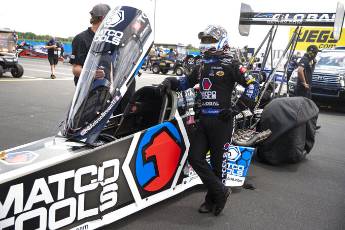 Antron Brown waits to climbs into his car for a run in Top Fuel during practice for an NHRA drag racing event in Brownsburg, Ind., Friday, July 10, 2020. The NHRA returned to action last weekend near Indianapolis, in front of fans, on network television and amid hopes of a quick financial rebound following a 138-day season suspension. It was the kind of boost everybody needed. Teams and crew members are scrambling to pay the bills. Big questions remain for the world's premier drag-racing series. The pandemic is still a threat to disrupt the season or shut it down again. (AP Photo/Michael Conroy)