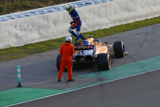 McLaren driver Lando Norris of Britain jumps from his car on the side of the track during a Formula One pre-season testing session at the Catalunya racetrack in Montmelo, outside Barcelona, Spain, Tuesday, Feb. 26, 2019. (AP Photo/Joan Monfort)