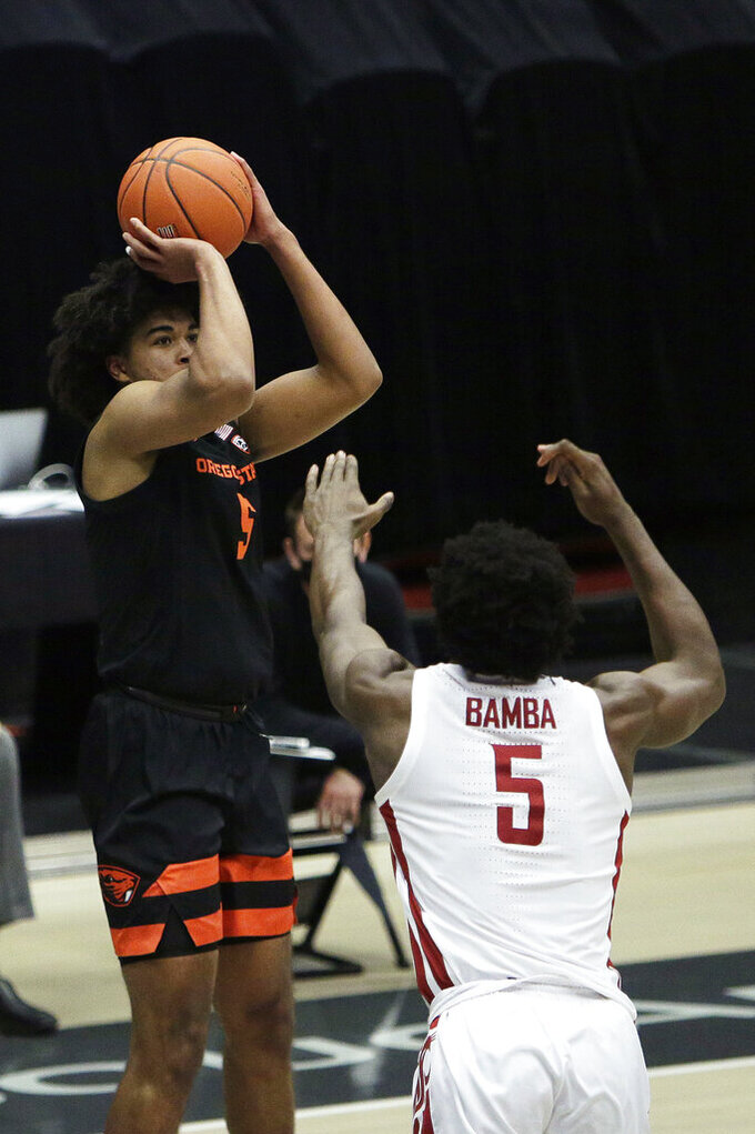Oregon State guard Ethan Thompson, left, shoots over Washington State guard TJ Bamba during the second half of an NCAA college basketball game in Pullman, Wash., Wednesday, Dec. 2, 2020. (AP Photo/Young Kwak)