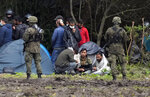 """Polish security forces surround migrants stuck along with border with Belarus in Usnarz Gorny, Poland, on Wednesday, Sept. 1, 2021. Poland has been reinforcing its border with Belarus – also part of the EU's eastern border – after thousands of migrants from Iraq, Afghanistan and elsewhere tried to illegally enter the country. The Polish government says it is the target of a """"hybrid war"""" waged by authoritarian Belarus. Human rights activists are concerned about a group caught along the border, trapped between armed guards on each side. (AP Photo/Czarek Sokolowski)"""