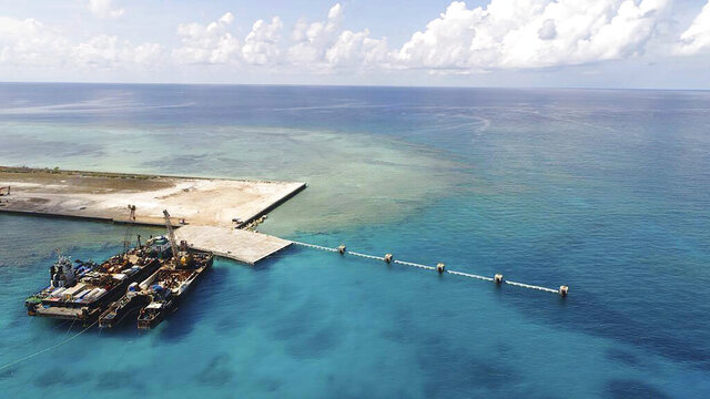 In this handout photo provided by the Department of National Defense PAS, ships carrying construction materials are docked at the newly built beach ramp at the Philippine-claimed island of Pag-asa, also known as Thitu, in the disputed South China Sea on Tuesday June 9, 2020. The Philippine defense chief and top military officials flew to a disputed island in the South China Sea Tuesday to inaugurate a beach ramp built to allow the