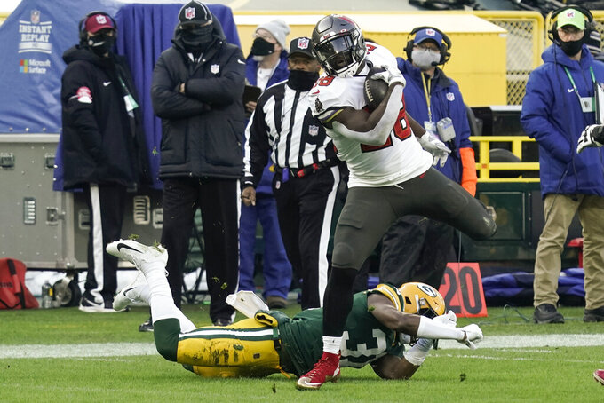 Tampa Bay Buccaneers' Leonard Fournette (28) evades a tackle by Green Bay Packers' Adrian Amos to score on a 20-yard touchdown run during the first half of the NFC championship NFL football game in Green Bay, Wis., Sunday, Jan. 24, 2021. (AP Photo/Morry Gash)