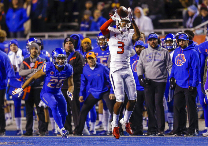 Fresno State wide receiver KeeSean Johnson (3) goes up for a reception in front of Boise State cornerback Avery Williams (26) during the first half of an NCAA college football game Friday, Nov. 9, 2018, in Boise, Idaho. (AP Photo/Steve Conner)