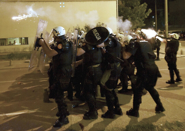 Montenegro police officers fire tear gas during protest in Podgorica, Montenegro, Wednesday, June 24, 2020. Seven police officers were injured and dozens protesters have been detained, including two lawmakers of the Democratic Front, in opposition riots that broke out in several Montenegrin cities on Wednesday. (AP Photo/Risto Bozovic)