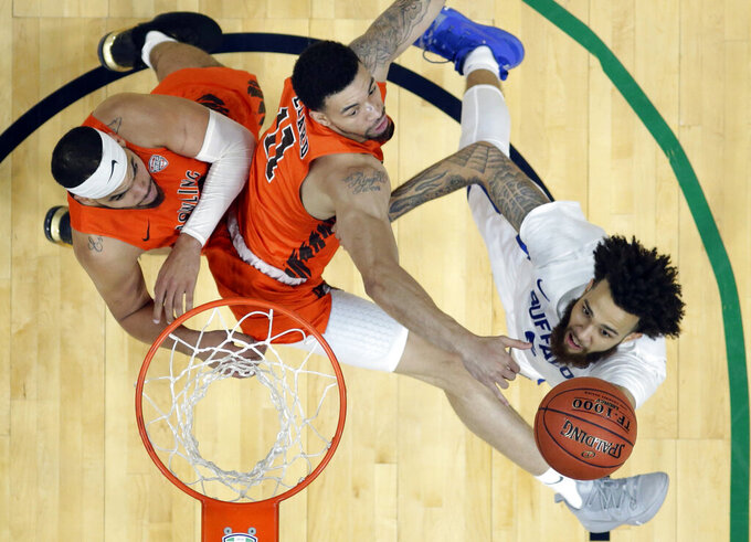 Buffalo's Jeremy Harris, right, drives to the basket against Bowling Green's Marlon Sierra, left, and Antwon Lillard, center, during the second half of an NCAA college basketball game for the Mid-American Conference men's tournament title Saturday, March 16, 2019, in Cleveland. Buffalo won 87-73. (AP Photo/Tony Dejak)