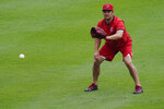 Cincinnati Reds pitcher Trevor Bauer warms up in the outfield during team baseball practice at Great American Ballpark in Cincinnati, Wednesday, July 8, 2020. (AP Photo/Bryan Woolston)