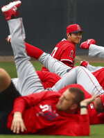 Los Angeles Angels' Shohei Ohtani smiles during a stretching exercise at a spring training baseball practice on Wednesday, Feb. 14, 2018, in Tempe, Ariz. (AP Photo/Ben Margot)