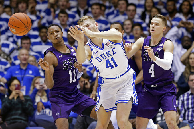 Stephen F. Austin guard Oddyst Walker (11) and guard David Kachelries (4) pressure Duke forward Jack White (41) during the first half of an NCAA college basketball game in Durham, N.C., Tuesday, Nov. 26, 2019. (AP Photo/Gerry Broome)