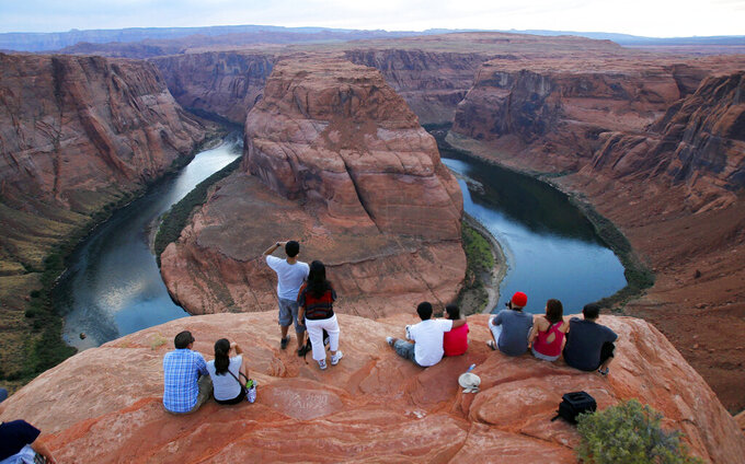 "FILE - In this Sept. 9, 2011 file photo visitors view the dramatic bend in the Colorado River at the popular Horseshoe Bend in Glen Canyon National Recreation Area, in Page, Ariz. Grand Canyon National Park officials tentatively plan to reopen the park's eastern entrance in late May 2021, but there's sentiment in the small northern Arizona city that depends on tourism that sooner would be better. ""Our sales tax for this year is down nearly 30% from last year,"" Page city manager Darren Coldwell told the Arizona Daily Sun. ""Our Horseshoe Bend visitation is down 80%. So when we say that our numbers dropped off the face of the earth, they really did.""  (AP Photo/Ross D. Franklin, File)"