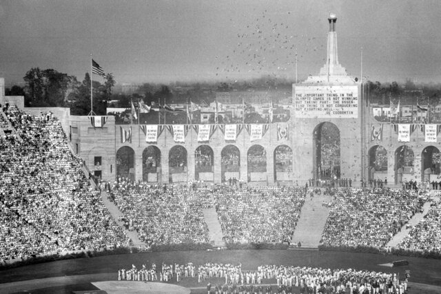 FILE - In this July 30, 1932, file photo, doves are released during the opening ceremony for the Tenth Olympiad at Los Angeles. The athletes of various countries are shown on the field while the Olympic beacon and the entrance to the stadium is shown in the background. (AP Photo/File)