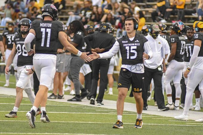 Jack Abraham, Southern Miss quarterback, high fives Thomas Morton, Southern Miss quarterback, as he comes off the field during their NCAA football game against the University of North Alabama Lions in Hattiesburg, Miss., Saturday, Nov. 7, 2020. (Cam Bonelli/Hattiesburg American via AP)