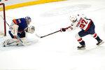 Washington Capitals center Evgeny Kuznetsov (92) scores against New York Islanders goaltender Semyon Varlamov (40) during the shootout in an NHL hockey game, Thursday, April 22, 2021, in Uniondale, N.Y. (AP Photo/Kathy Willens)