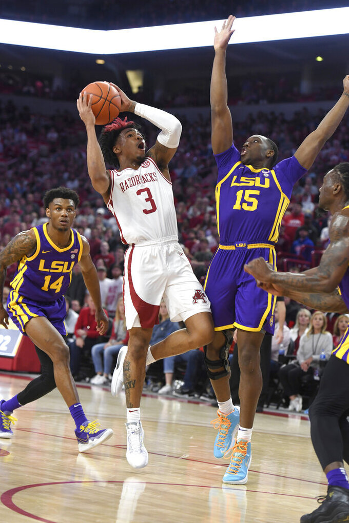 FILE - Arkansas guard Desi Sills (3) drives past LSU defenders Marlon Taylor (14) and Aundre Hyatt (15) during the first half of an NCAA college basketball game in Fayetteville, Ark., in this Wednesday, March 4, 2020, file photo. Arkansas will have a distinctly different look this season. Isaiah Joe and Mason Jones left school early and declared for the NBA Draft, leaving the Razorbacks without their combined 39 points per game. Sills, one of the returnees, averaged 12.4 points over the final 14 games last season. (AP Photo/Michael Woods, FIle)