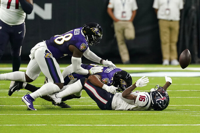 Baltimore Ravens cornerback Marlon Humphrey, center, causes Houston Texans wide receiver Keke Coutee (16) to fumble during the first half of an NFL football game Sunday, Sept.20, 2020, in Houston. Baltimore recovered the ball and scored a touchdown on the play. (AP Photo/David J. Phillip)