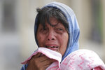 Erman Batan breaks in tears over her missing husband Roberto who she has not seen since they evacuated their homes near the Taal volcano in Tagaytay, Cavite province, southern Philippines on Monday, Jan. 13, 2020. (AP Photo/Aaron Favila)