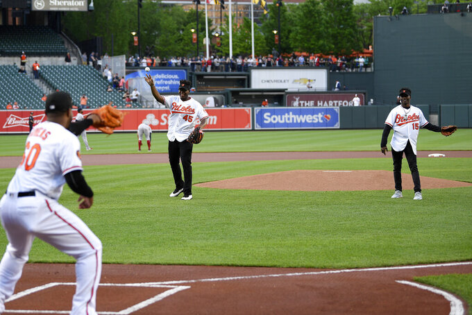 Baltimore Ravens NFL football draft picks Jaylon Ferguson, top left, and Marquise Brown, top right, throw out ceremonial first pitches to Baltimore Orioles' Mychal Givens (60) before a baseball game against the Boston Red Sox, Monday, May 6, 2019, in Baltimore. (AP Photo/Nick Wass)