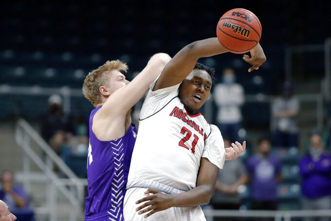 Nicholls State center Ryghe Lyons (21) passes the ball in front of Abilene Christian center Kolton Kohl, left, during the first half of an NCAA college basketball game for the Southland Conference men's tournament championship Saturday, March 13, 2021, in Katy, Texas. (AP Photo/Michael Wyke)