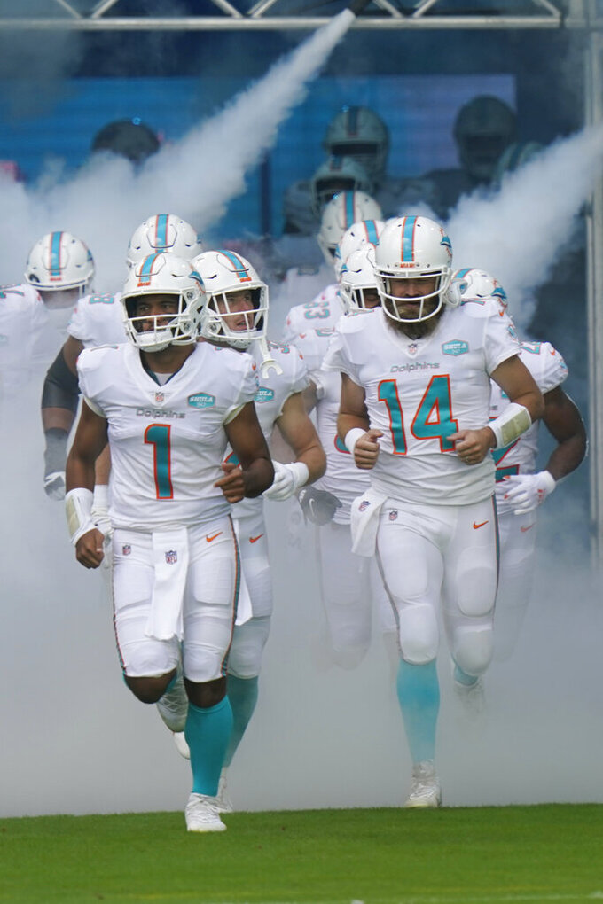 Miami Dolphins quarterbacks Tua Tagovailoa (1) and quarterback Ryan Fitzpatrick (14) enter the field, during the first half of an NFL football game against the Los Angeles Rams, Sunday, Nov. 1, 2020, in Miami Gardens, Fla. This is quarterback Tua Tagovailoa's first game as the starting quarterback. (AP Photo/Lynne Sladky)