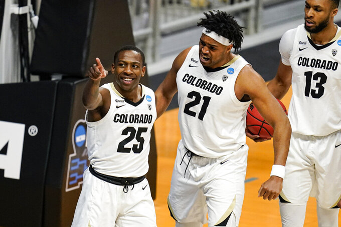 Colorado guard McKinley Wright IV (25) celebrates with forward Evan Battey (21) and forward Dallas Walton (13) in the second half of a first-round game against Georgetown in the NCAA men's college basketball tournament at Hinkle Fieldhouse in Indianapolis, Saturday, March 20, 2021. (AP Photo/Michael Conroy)