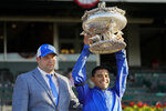 Jockey Luis Saez, right, holds up the August Belmont Trophy with Brad Cox after winning the 153rd running of the Belmont Stakes horse race with Essential Quality (2), Saturday, June 5, 2021, at Belmont Park in Elmont, N.Y. (AP Photo/John Minchillo)