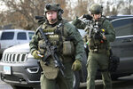 Police officers armed with rifles gather at the scene where an active shooter was reported in Aurora, Ill., Friday, Feb. 15, 2019. (Antonio Perez/Chicago Tribune via AP)