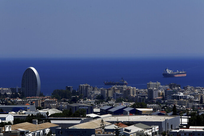 FILE - This Friday, July 6, 2018 file photo, shows the Oval building, left, one of a number of new high-rises transforming the skyline view, of the southern coastal city of Limassol in the eastern Mediterranean island of Cyprus. Cyprus government spokesman Kyriakos Koushos said on Tuesday, Oct. 13, 2020, that the Cabinet accepted a recommendation by the minsters of the interior and finance to cancel altogether the