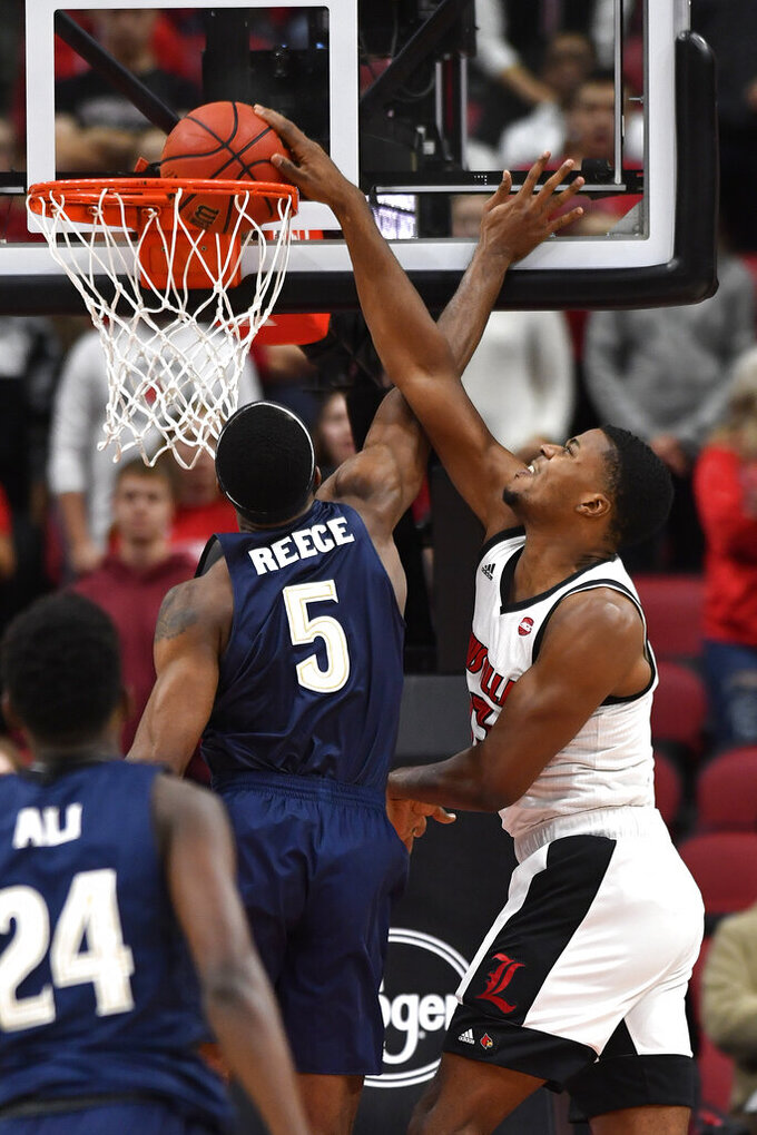 Louisville center Steven Enoch, right, scores over the defense of Akron forward Camron Reece (5) during the first half of an NCAA college basketball game in Louisville, Ky., Sunday, Nov. 24, 2019. (AP Photo/Timothy D. Easley)