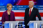 Democratic presidential candidate Sen. Elizabeth Warren, D-Mass., speaks as Democratic presidential candidate former Vice President Joe Biden listens during a Democratic presidential primary debate, Wednesday, Nov. 20, 2019, in Atlanta. (AP Photo/John Bazemore)