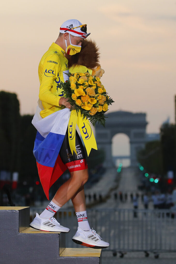 Tour de France winner Slovenia's Tadej Pogacar, wearing the overall leader's yellow jersey, holds the Slovenian flag as he walks off the podium after the twenty-first and last stage of the Tour de France cycling race over 122 kilometers (75.8 miles), from Mantes-la-Jolie to Paris, France, Sunday, Sept. 20, 2020. (AP Photo/Christophe Ena)