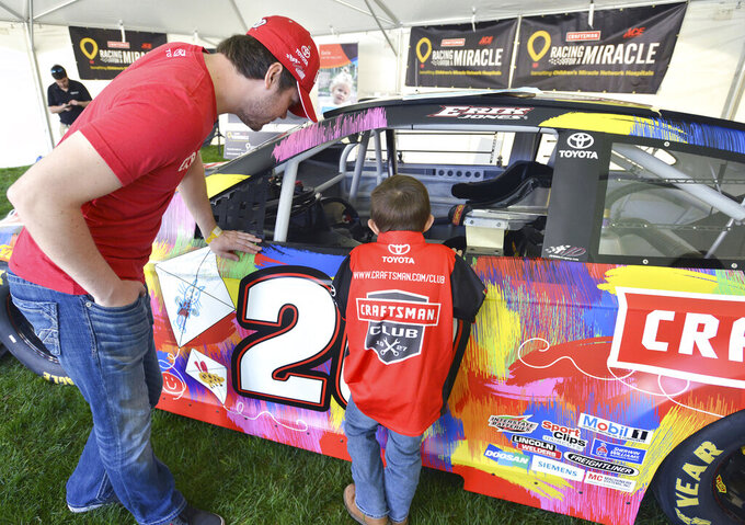 "Gavin Brewer, a 4-year old leukemia patient at Niswonger Children's Hospital in Johnson City, Tenn., talks with Nascar driver Erik Jones after the press conference in Johnson City, Tenn., compares her original drawing with the one on Erik Jones' Toyota, Thursday, April 4, 2019. Four patients from Niswonger helped design Jones' car for this weekend's race at Bristol Motor Speedway. Jones and the Ace Hardware Foundation as part of the Stanley Black & Decker ""Racing for a Miracle"" program presented a $100,000 check to hospital that could become a $1 million dollar check in Jones wins on Sunday. (David Crigger/Bristol Herald Courier via AP)"