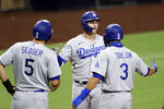 Los Angeles Dodgers' Joc Pederson, center, is greeted by Chris Taylor (3) and Corey Seager (5) after hitting a three-run home run during the sixth inning of a baseball game against the San Diego Padres, Wednesday, Aug. 5, 2020, in San Diego. (AP Photo/Gregory Bull)