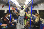 People ride a Northern Line train in London after the 10 p.m. curfew pubs and restaurants are subject to in order to combat the rise in coronavirus cases in England, on Saturday Oct. 3, 2020. (Victoria Jones/PA via AP)