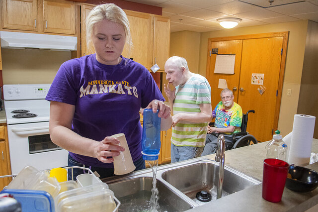 In this Feb. 27, 2020 photo, Wylie Rollings does the dishes in the kitchen in a community room at the Harry Meyering Center in Mankato, Minn., as residents Michael Dreyer and Richard Anderson, right, mull about behind her. (Jackson Forderer/The Free Press via AP)