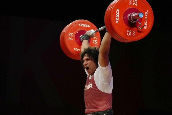 CORRECTS LAST NAME TO ELBAKH FROM ELBACH - Fares Elbakh of Qatar ccompetes in the men's 81kg weightlifting event, at the 2020 Summer Olympics, Saturday, July 31, 2021, in Tokyo, Japan. (AP Photo/Luca Bruno)