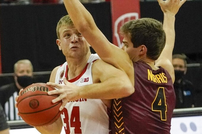 Wisconsin's Brad Davison tries to get past Loyola's Braden Norris during the first half of an NCAA college basketball game Tuesday, Dec. 15, 2020, in Madison, Wis. (AP Photo/Morry Gash)