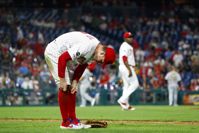 Philadelphia Phillies first baseman Rhys Hoskins adjusts his uniform after committing an error on a run-scoring grounder by Pittsburgh Pirates' Kevin Newman during the ninth inning of a baseball game Tuesday, Aug. 27, 2019, in Philadelphia. Pittsburgh won 5-4. (AP Photo/Matt Slocum)