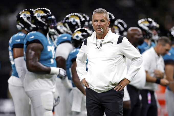 FILE - In this Monday, Aug. 23, 2021, file photo, Jacksonville Jaguars head coach Urban Meyer watches as his team warms up before a preseason NFL = football game against the New Orleans Saints in New Orleans. In many regards, Meyer runs the Jaguars like a college program It's what he knows even though he spent a year studying the NFL before he ended a brief coaching retirement. It's also worked at every previous stop, so no one is questioning his methods. (AP Photo/Brett Duke, File)
