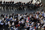 Riot police stand guard as retired Lebanese soldiers try to remove a barbed wire barrier to advance towards the government building during a protest, in Beirut, Lebanon, Monday, May 20, 2019. Lebanese security forces have opened heavy water cannons on anti-austerity protests in the capital city, as the government faces a looming fiscal crisis. Over one hundred protesters gathered Monday outside the Government House in downtown Beirut shouting