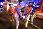 FILE - In this Nov. 13, 2015, file photo, a woman is being evacuated from the Bataclan concert hall after a shooting in Paris. France is putting on trial 20 men accused in the Nov. 13, 2015, Islamic State terror attacks on Paris that left 130 people dead and hundreds injured. Nine gunmen and suicide bombers struck within minutes of each other at the national soccer stadium, the Bataclan concert hall and restaurants and cafes. (AP Photo/Thibault Camus, File)